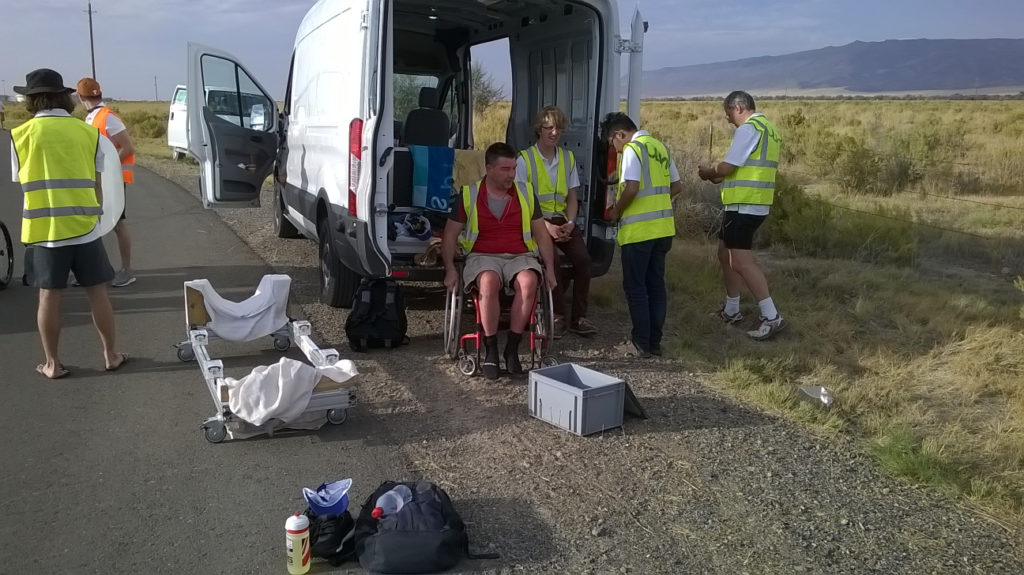 Handcyclists sits in the shade of a van