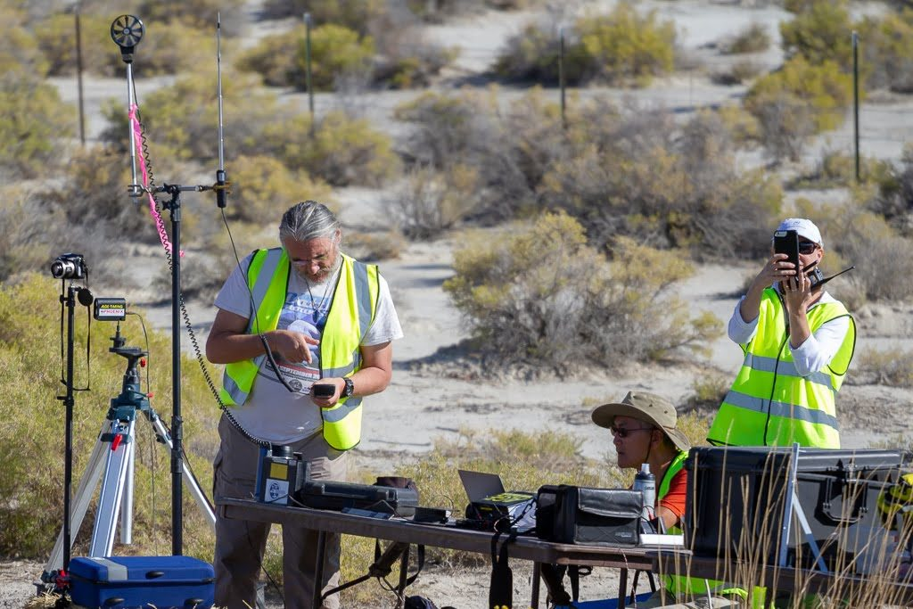 People chack wind and data at a table in the desert